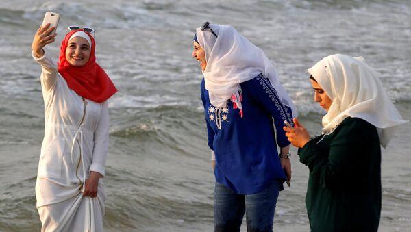 Девушки в хиджабах делают селфи на одном из пляжей Тель-Авива - Sputnik Italia