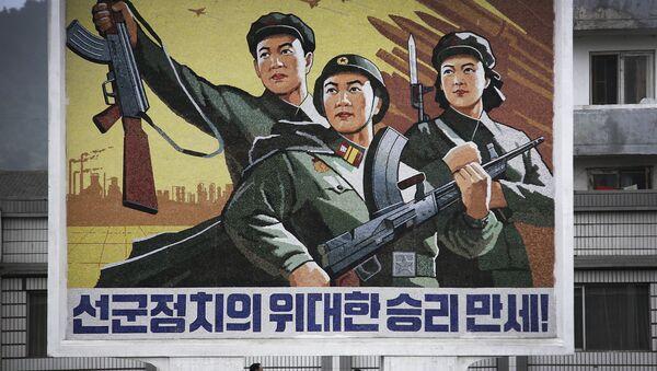 Corea del Nord, la gente passa sotto il poster Evviva la vittoria della politica dell'esercito prima di tutto nel centro della città di Wonsan. - Sputnik Italia