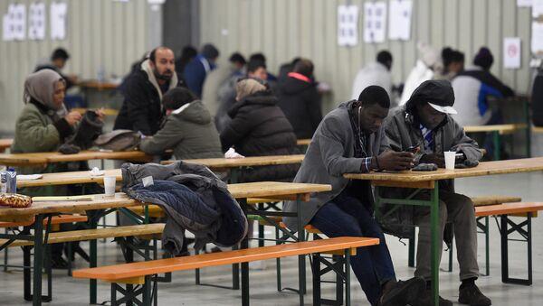 Immigrati usano i loro telefoni in una mensa nella bassa sassonia - Sputnik Italia