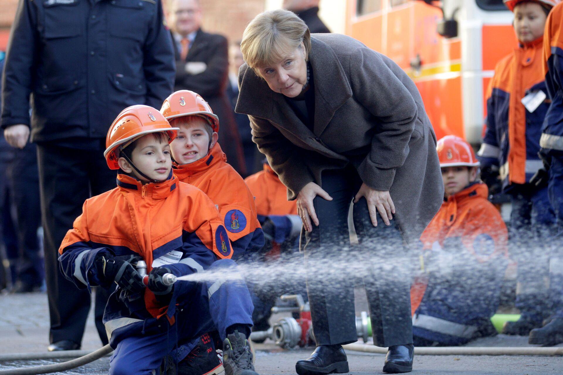 Angela Merkel con due piccoli vigili del fuoco - Sputnik Italia, 1920, 11.10.2021