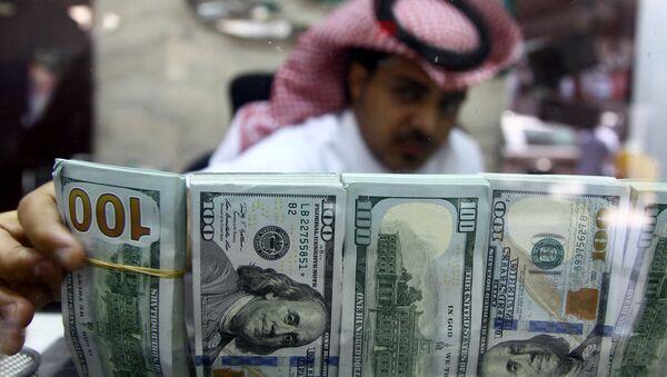 A Saudi money changer, pictured through a glass, arranges U.S banknotes at a currency exchange shop in Riyadh, Saudi Arabia September 29, 2016 - Sputnik Italia