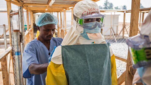 Медработник застегивает защитное снаряжение коллеги перед входом к больным вирусом Эбола в клинике в Макени, Сьерра-Леоне - Sputnik Italia