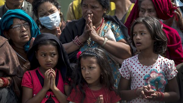 Local residents pray as they queue up for relief supplies distributed by international aid organisation after the April 25 earthquake in Bhaktapur, Nepal, May 10, 2015 - Sputnik Italia