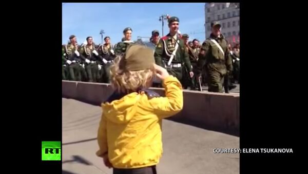 Un bimbo saluta le truppe durante la Parata della Vittoria il 9 maggio. - Sputnik Italia