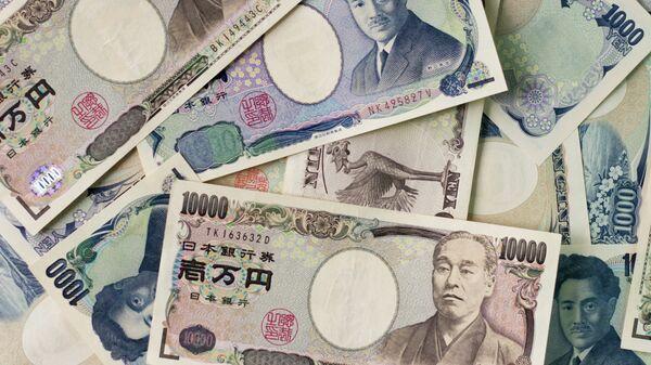 1000 yen bills and 10,000 yen bills spread out on a table. - Sputnik Italia