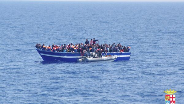 Italian Navy on Sunday, June 15, 2014, and taken on Saturday, June 14, 2014, a boat filled with migrants receives aid from an Italian Navy motor boat off the coast of Sicily, Italy. The Italian coast guard and navy have rescued more than 300 migrants. - Sputnik Italia