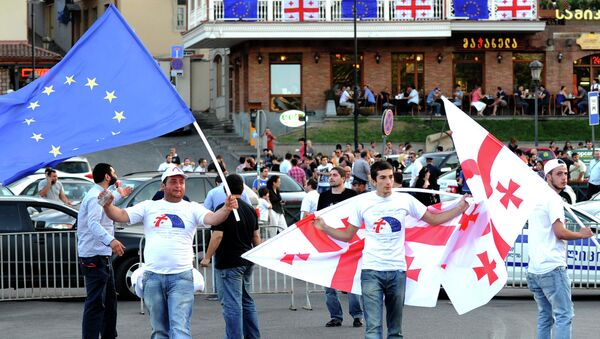 People wave the flags of Georgia (R) and the European Union (L) during celebrations for the signing of an association agreement with the EU in Tbilisi on June 27, 2014 - Sputnik Italia