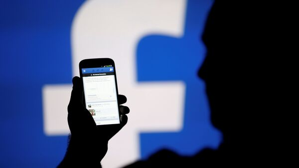 A man is silhouetted against a video screen with a Facebook logo - Sputnik Italia