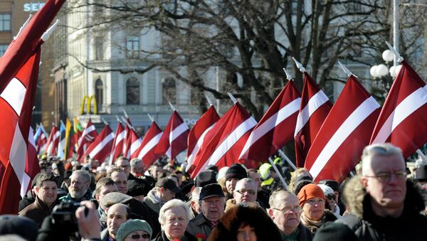 People carry Latvian flags at the march in Riga, Latvia - Sputnik Italia