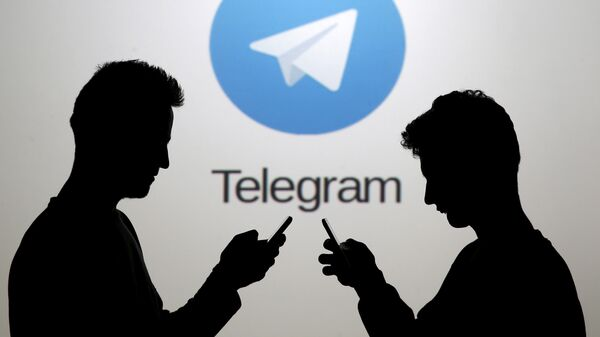 Men pose with smartphones in front of a screen showing the Telegram logo in this picture illustration November 18, 2015. - Sputnik Italia