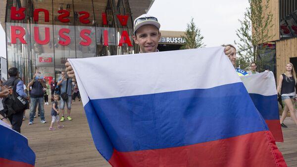 Un visitatore con la bandiera della Russia posa davanti al padiglione russo dell'EXPO di Milano - Sputnik Italia