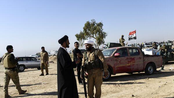 Members of Al-Hashd al-Shaabi faction talk on October 21, 2016, near the village of Tall al-Tibah, some 30 kilometres south of Mosul, during an operation to retake the main hub city from the Islamic State (IS) group jihadists - Sputnik Italia