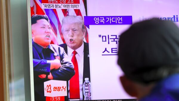 A man watches a television news programme showing US President Donald Trump (C) and North Korean leader Kim Jong-Un (L) at a railway station in Seoul on August 9, 2017 - Sputnik Italia