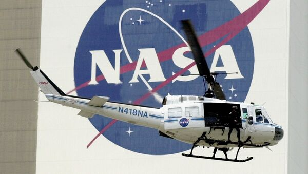 A NASA security helicopter flies by the NASA logo on the Vehicle Assembly Building - Sputnik Italia