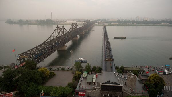 The sun sets over the Friendship bridge on the Yalu River connecting the North Korean town of Sinuiju and Dandong in Chinese border city of Dandong on July 5, 2017 - Sputnik Italia