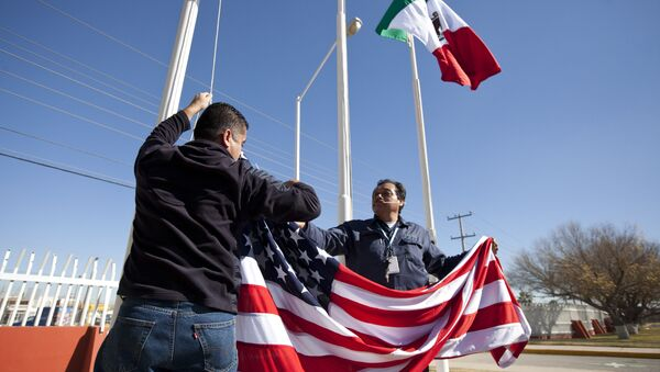 In this Friday, Dec. 27, 2013 photo, workers at one of maquiladoras of the TECMA group prepare to raise the U.S. flag along with the Mexican and TECMA flags in Ciudad Juarez, Mexico - Sputnik Italia