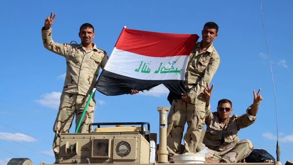 Iraqi government forces wave the national flag from their vehicles in the village of Mohammadi, a few miles north of Heet, in Iraq's western province of Anbar on March 18, 2016. - Sputnik Italia