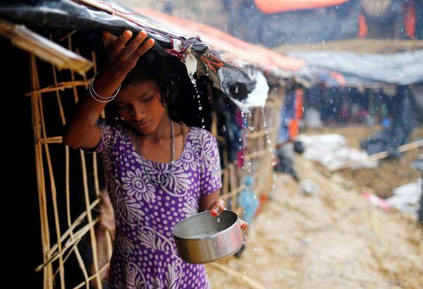 Una ragazza rifugiata raccoglie l'acqua di pioggia in Bangladesh. - Sputnik Italia