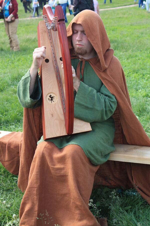 Un figurante al festival Vremena i Epohi suona un'antica arpa. - Sputnik Italia