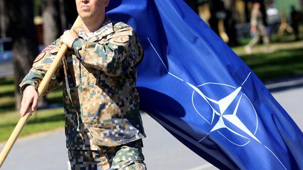 Militare lettone con la bandiera della NATO - Sputnik Italia