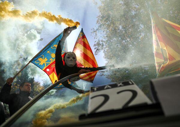 Un uomo in maschera tiene un fumogeno durante lo sciopero dei taxi a Madrid. - Sputnik Italia