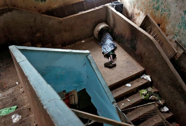 Un mendicante dorme sulle scale in un mercato di Bengaluru, India. - Sputnik Italia