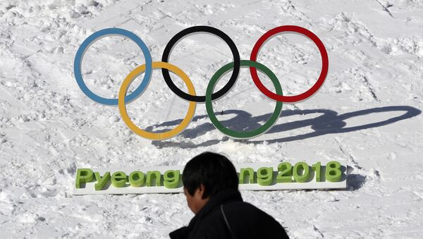 In this Feb. 3, 2017 photo, a man walks by the Olympic rings with a sign of 2018 Pyeongchang Olympic and Paralympic Winter Games in Pyeongchang, South Korea - Sputnik Italia