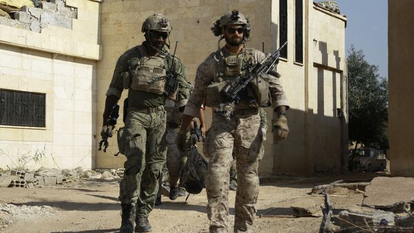 Armed men in uniform identified by Syrian Democratic forces as US special operations forces walk in the village of Fatisah in the northern Syrian province of Raqa on May 25, 2016 - Sputnik Italia