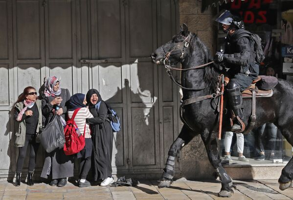 Donne spaventate stanno vicino al poliziotto israeliano armato a Gerusalemme est. - Sputnik Italia
