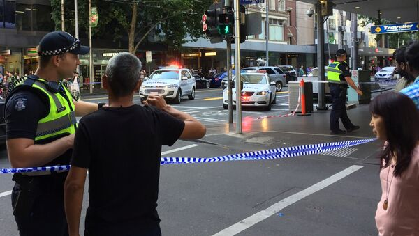 Police officers stand guard as members of the public stand behind police tape after the arrest of the driver of a vehicle that ploughed into pedestrians at a crowded intersection near the Flinders Street train station in central Melbourne, Australia December 21, 2017 - Sputnik Italia