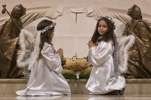 Bambine vestite da angeli pregano a Natale, Kosovo. - Sputnik Italia