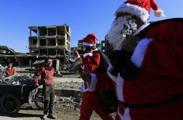 Un bambino siriano sorride agli uomini vestiti da Babbo Natale, Raqa, Siria. - Sputnik Italia