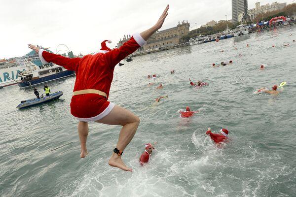 Un partecipante vestito da Babbo Natale durante una nuotata di Copa Nadal a Barcellona. - Sputnik Italia