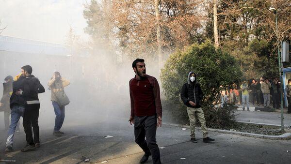 Iran, university students attend a protest inside Tehran University while a smoke grenade is thrown by anti-riot Iranian police, in Tehran, Iran, Saturday, Dec. 30, 2017 - Sputnik Italia