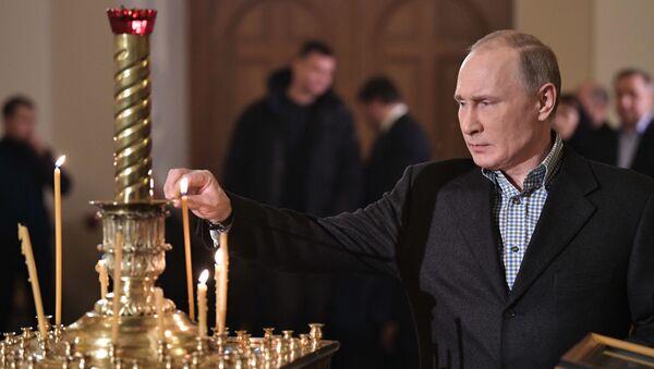 Il presidente russo Vladimir Putin durante la Messa di Natale presso la chiesa dei santi Simeone e Anna a San Pietroburgo. - Sputnik Italia