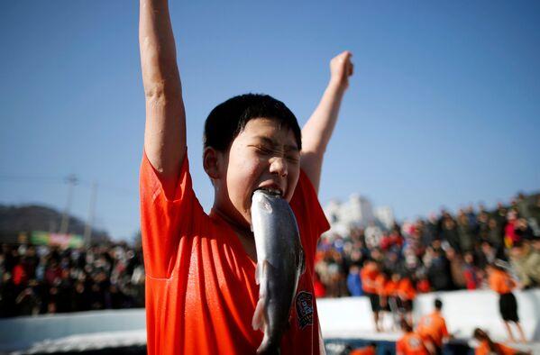 Un ragazzo ha catturato una trota a Hwacheon, Corea del Sud. - Sputnik Italia