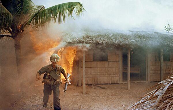 Американский солдат на фоне горящего дома. Война во Вьетнаме - Sputnik Italia