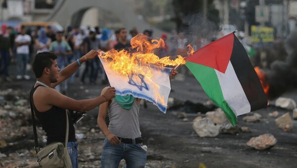 A Palestinian protester burns a replica Israeli flag as another holds a Palestinian flag during clashes with the Israeli troops near the Jewish settlement of Bet El, near the West Bank city of Ramallah October 18, 2015 - Sputnik Italia