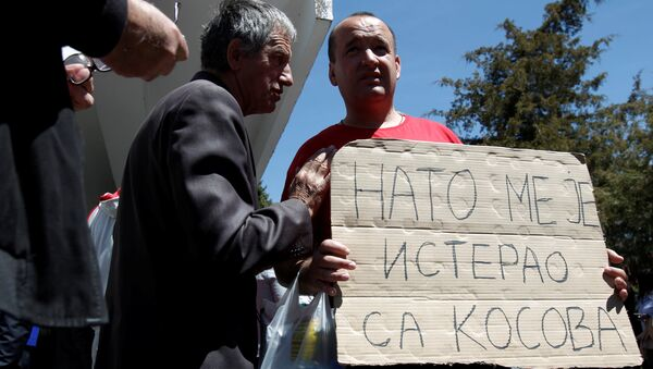 A protester holds a banner that reads NATO forced me out of Kosovo after a protest described as a parallel parliament, ahead of April 28's parliament vote to ratify the Montenegro's NATO membership, in the village of Murino, Montenegro, April 26, 2017 - Sputnik Italia