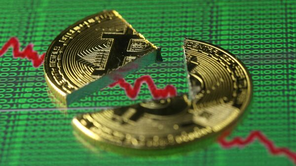 Broken representation of the Bitcoin virtual currency, placed on a monitor that displays stock graph and binary codes, are seen in this illustration picture, December 21, 2017 - Sputnik Italia