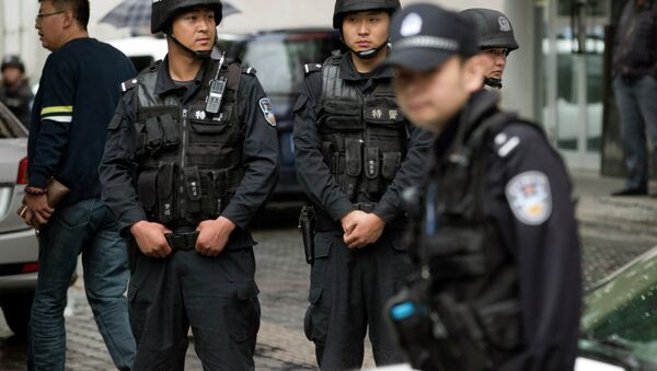 Armed policemen stand guard near the site of an explosion in Urumqi, northwest China's Xinjiang region, Thursday, May 22, 2014 - Sputnik Italia