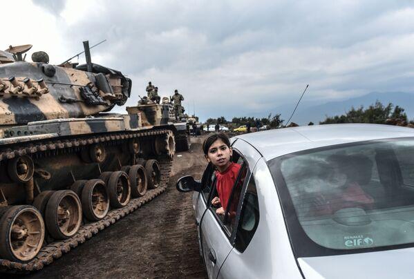 Una ragazza turca osserva i carri armati e soldati dell'esercito turco arrivare al confine siriano a Hassa. - Sputnik Italia