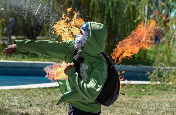 Un manifestante lancia una bottiglia Molotov contro la polizia durante gli scontri a Caracas, iniziati dopo l'eliminazione dell'ex poliziotto Oscar Perez. - Sputnik Italia