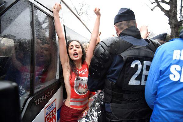 Una partecipante al Femen sta di fronte a un poliziotto alla Marcia per la vita a Parigi. - Sputnik Italia