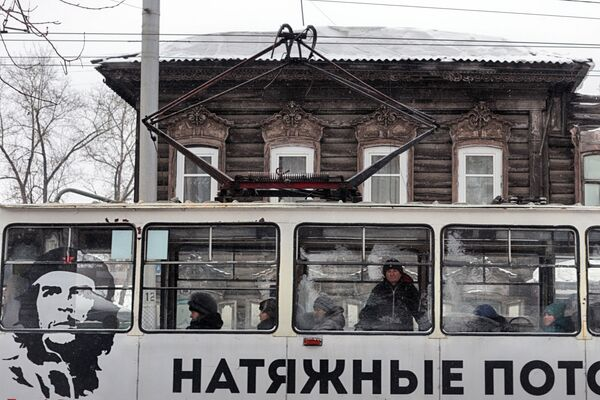 Una casa di legno e la pubblicità su un tram ad Irkutsk. - Sputnik Italia