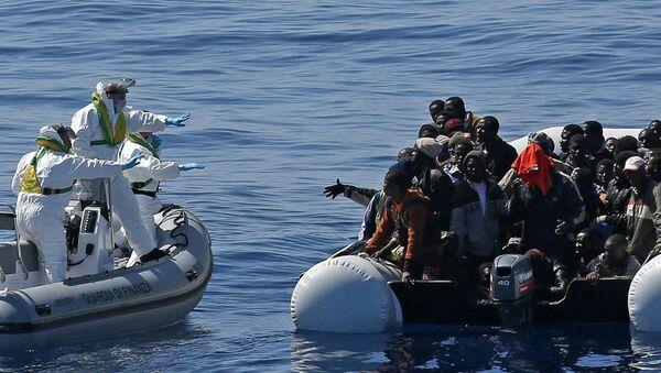 Agenti della Guardia di finanza soccorre i migranti al largo delle coste della Libia - Sputnik Italia