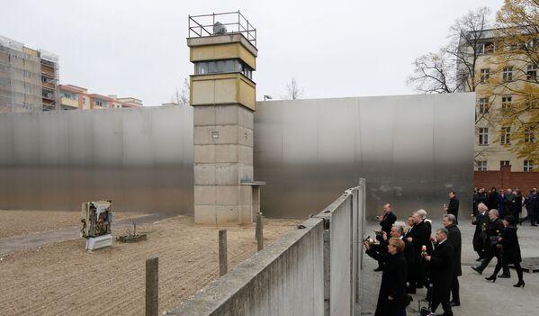 La cancelliera tedesca Angela Merkel depone fiori al Muro di Berlino. - Sputnik Italia