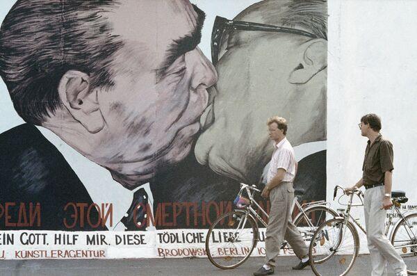 Berlinesi guardano una parte del Muro di Berlino rimasta indistrutta dipinta da un pittore. - Sputnik Italia
