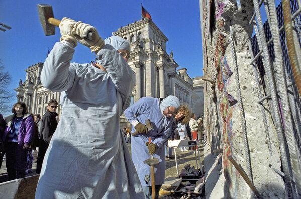 Gli abitanti della Germania Est si prendono i souvenir dal Muro di Berlino, 1990. - Sputnik Italia