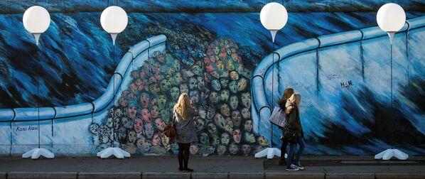 La gente sta vicino ai stand colorati con palloni luminosi, un'installazione al posto dove si trovava il Muro di Berlino. - Sputnik Italia
